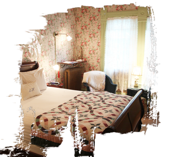 The rose room has rose patterned wallpaper and a blanket on the end of the bed with clean white linens