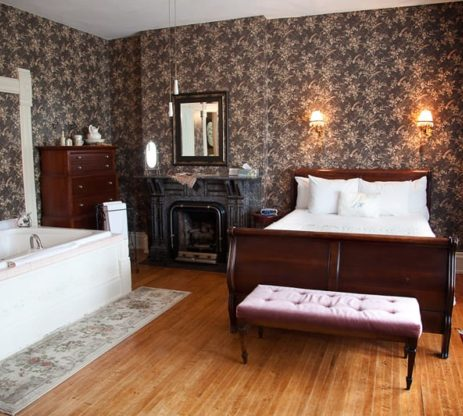 The Master Suite has a large jacuzzi and a dark wood sleigh bed next to a fireplace.