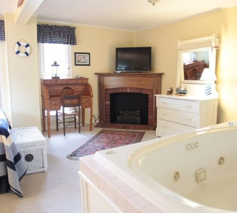 The nautical room has a jacuzzi, fireplace, desk, and bed all in the same room