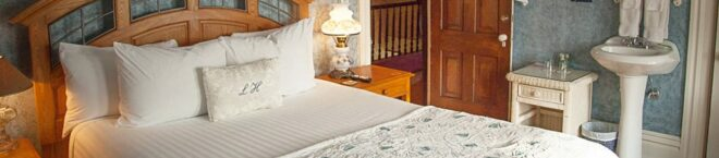 The Blue Room has blue textured wallpaper and a bed with a nice oak headboard
