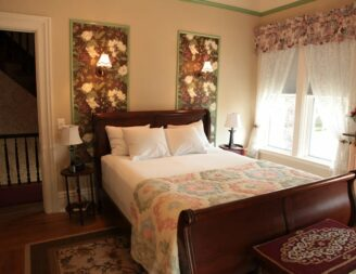 The Corner Room has a dark wood sleigh bed and is decorated with florals
