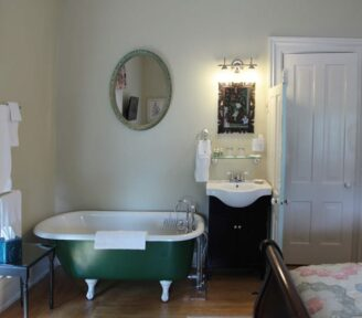The bathroom in the Corner Room has a nice green clawfoot tub with an old style sink