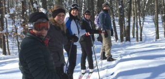 Friends snowshoe through the winter woods nearby Ludington