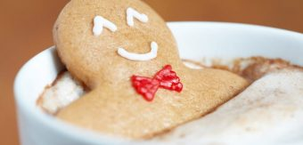 A gingerbread cookie man is relaxing in a hot cup of coffee