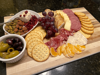 charcuterie board loaded with meats, cheeses and fruit