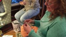 Two women knit together inside the Ludington House for the Knitters weekend