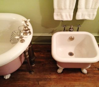 The bathtub and sink inside the rose room are nice and clean and there are solid wood floors