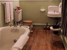 The bathroom inside the rose room has wood floors an a clawfoot tub