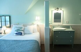 Bed and bathroom area in blues and greens