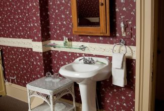 Red crimson wallpaper and an oak cabinet above the sink in the skylight room