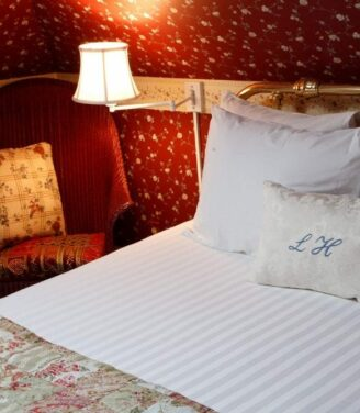 The lamp next to the bed in the skylight room lights up the crimson red wallpaper and clean white linens