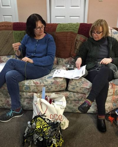 Two friends knitting side by side and discussing tecnique