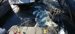 Looking down from atop of the ship water is bubbling up from the engine