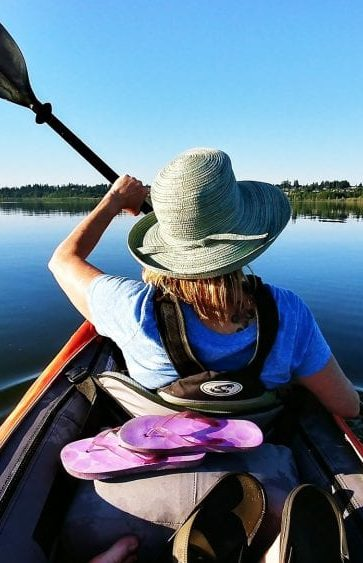 Woman canoeing on peaceful water.